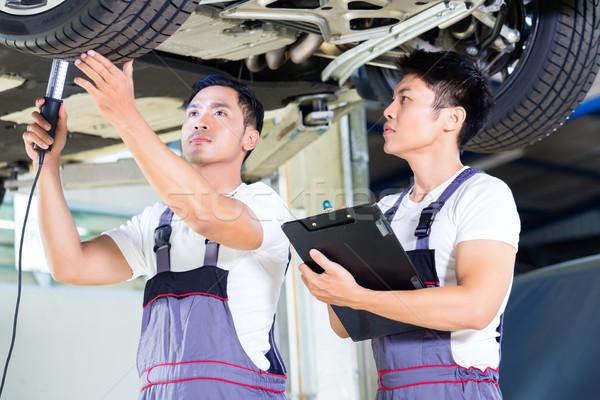 Car mechanics checking floor of luxury car on hoist Stock photo © Kzenon