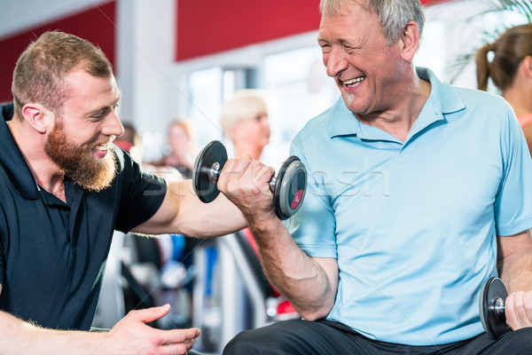 Senior man working out with personal trainer at the gym Stock photo © Kzenon