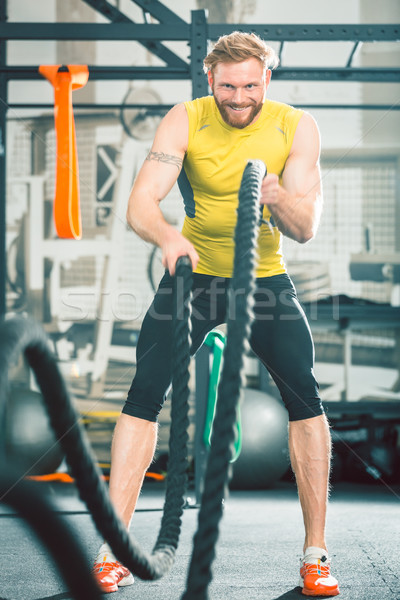 Handsome bodybuilder exercising with battle ropes during functional training Stock photo © Kzenon
