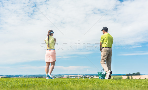 Young woman practicing the correct move during golf class outdoors Stock photo © Kzenon