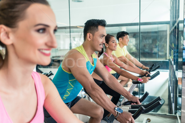 Beautiful fit woman smiling during workout at indoor cycling group class Stock photo © Kzenon