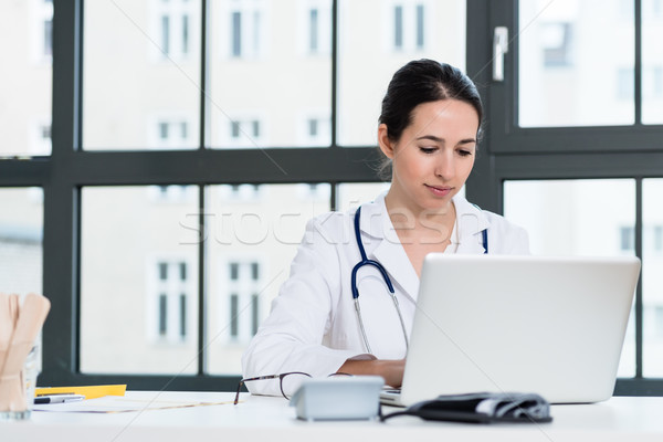 Portrait of young female physician working on laptop in the office Stock photo © Kzenon