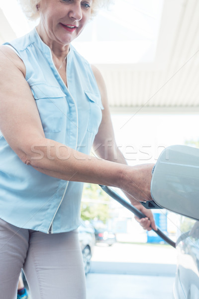 Active senior woman smiling while filling up the gas tank of her car Stock photo © Kzenon
