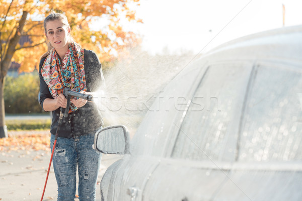 Woman cleaning her vehicle in self-service car wash Stock photo © Kzenon