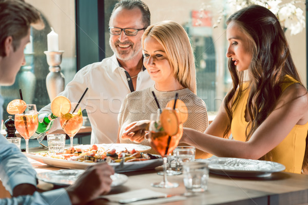 Blond beautiful woman having lunch with her best friends at a trendy restaurant Stock photo © Kzenon