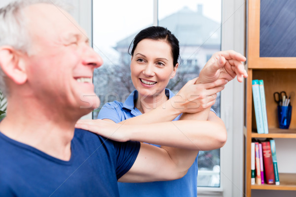 Elderly patient doing shoulder workout under assistance of therapist Stock photo © Kzenon