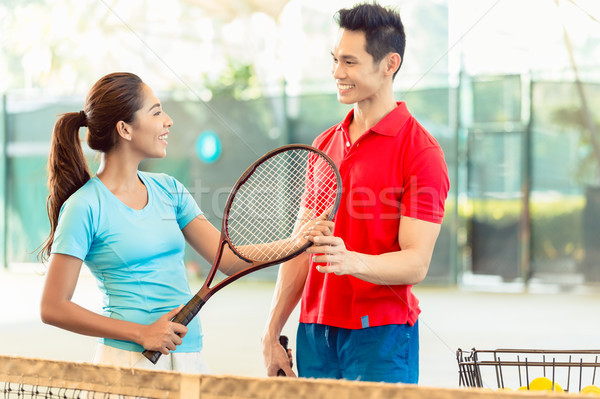 Tennis instructor teaching a beginner player the correct grip Stock photo © Kzenon