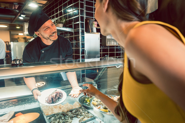 Experienced chef choosing raw seafood from the freezer for two customers Stock photo © Kzenon