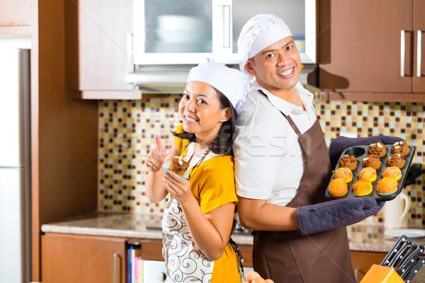 Asian couple baking muffins in home kitchen Stock photo © Kzenon