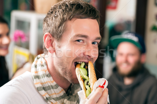 Customer eating Hotdog in fast food snack bar Stock photo © Kzenon