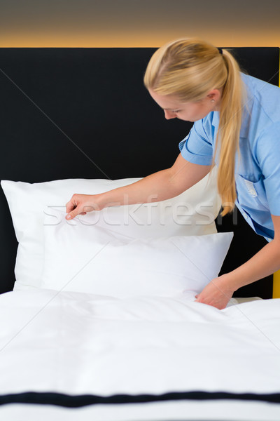 Service in hotel, maid puts clean sheets on bed Stock photo © Kzenon