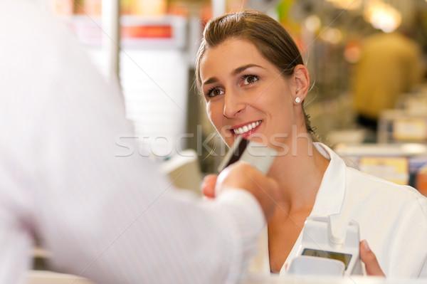 Cashier in supermarket taking credit card Stock photo © Kzenon