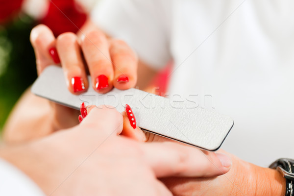 Man in nail salon receiving manicure Stock photo © Kzenon
