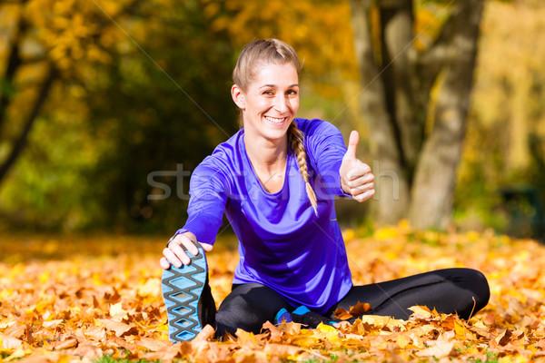 Sportswoman sport stretching in autumn leaves Stock photo © Kzenon