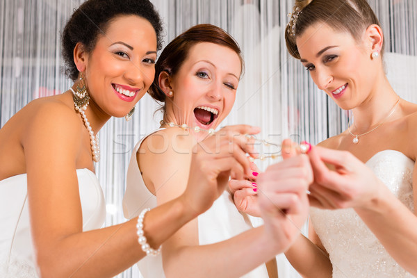 Women having fun while bridal dress fitting in shop Stock photo © Kzenon