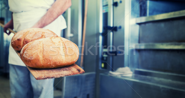 Baker in bakery with bread on shovel Stock photo © Kzenon