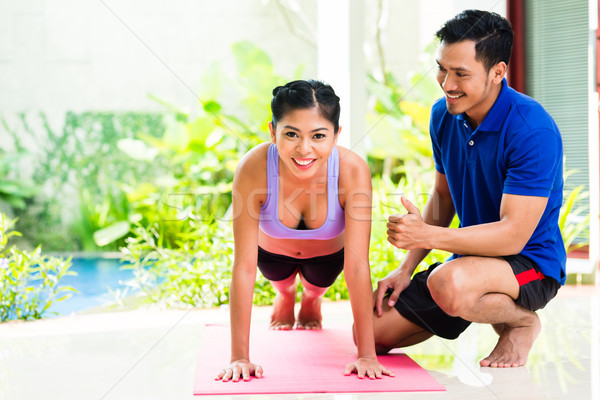 Asian woman and personal trainer at sport exercise Stock photo © Kzenon