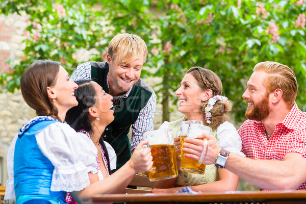 Friends clinking glasses in beer garden Stock photo © Kzenon