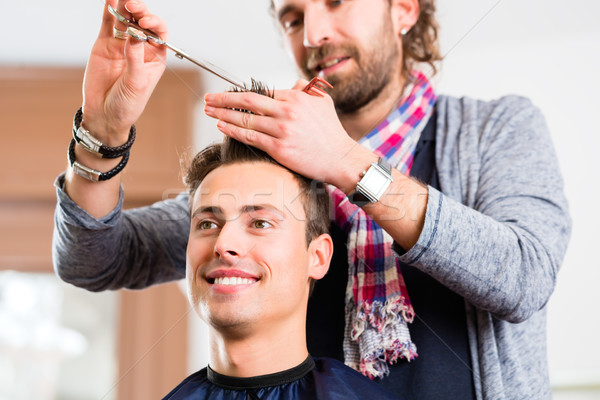 Barber trimming man hair in haircutter shop Stock photo © Kzenon