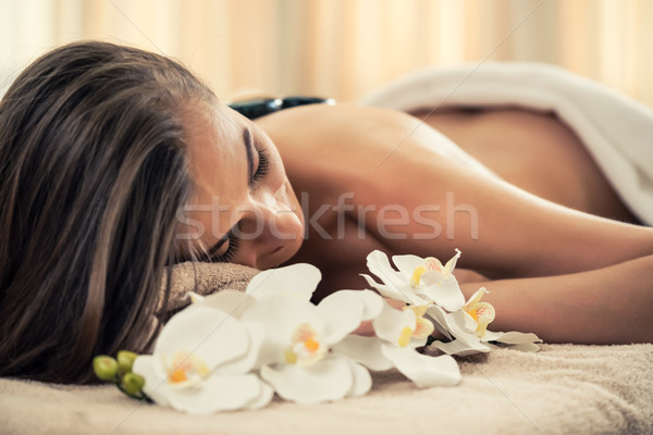 Young woman lying down with traditional hot stones along the spi Stock photo © Kzenon