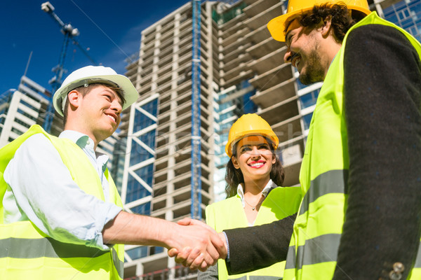 Architects and foreman in meeting at construction site Stock photo © Kzenon