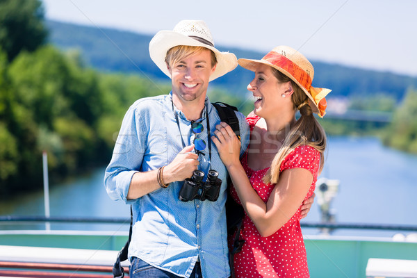 Happy couple on river cruise in summer wearing sun hats Stock photo © Kzenon