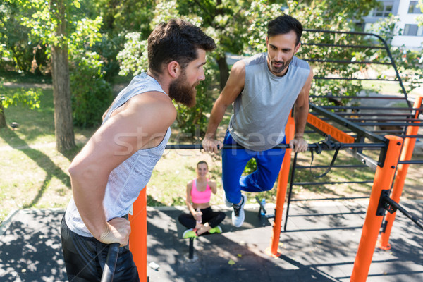Two muscular young men doing bodyweight exercises in a modern fi Stock photo © Kzenon