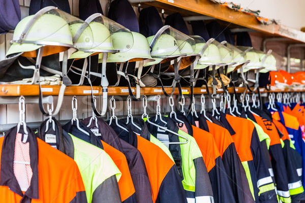 Helmets and uniforms in arsenal of fire fighters Stock photo © Kzenon