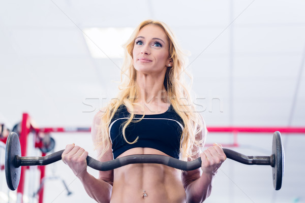 Woman with barbell doing sport in fitness gym Stock photo © Kzenon