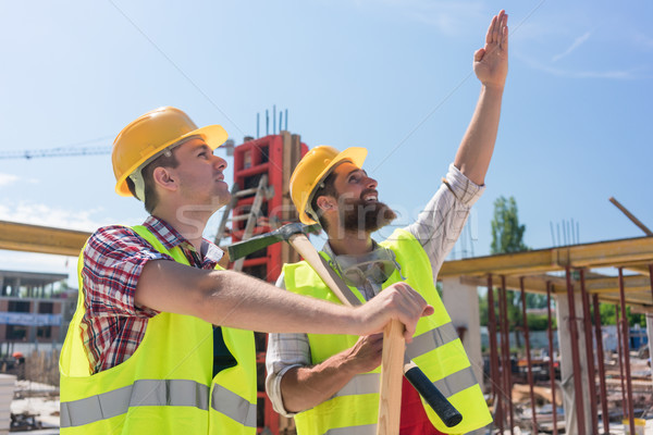 Determined young worker pointing up while imagining the height of a building Stock photo © Kzenon