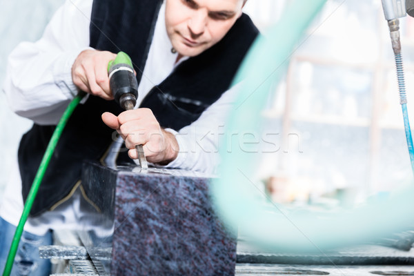 Stonemason working with pneumatic chisel Stock photo © Kzenon