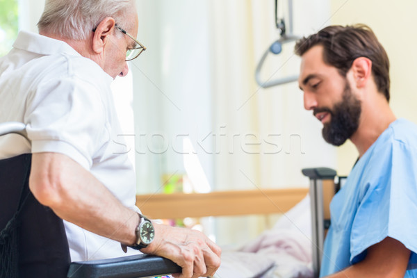 Elderly care nurse helping senior from bed to wheel chair  Stock photo © Kzenon