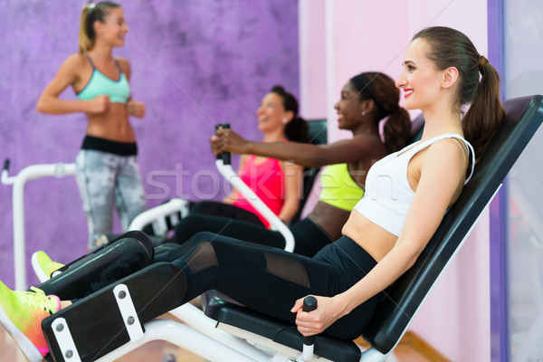 Beautiful woman smiling while exercising at the hip abductor machine Stock photo © Kzenon