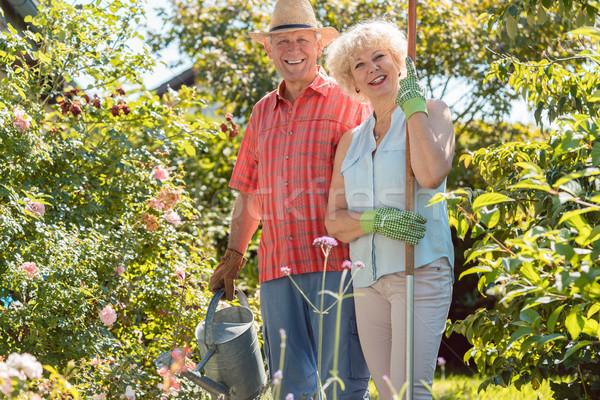 Active happy senior woman standing next to her husband during garden work Stock photo © Kzenon