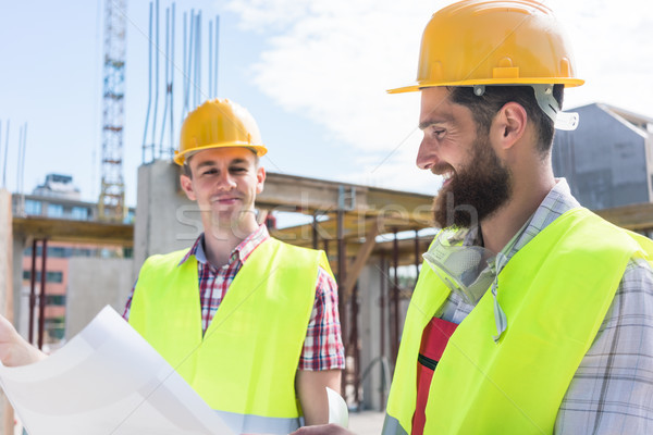 Two young construction workers analyzing together a plan Stock photo © Kzenon