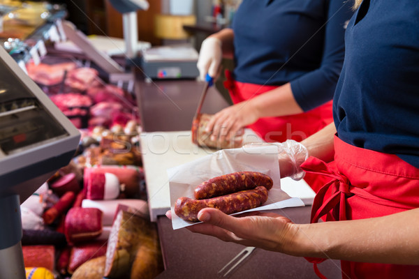 Sales women in butcher shop selling meat and sausages Stock photo © Kzenon