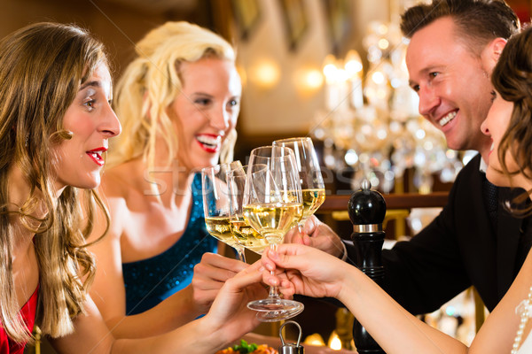 Stock photo: Friends in a very good restaurant clink glasses