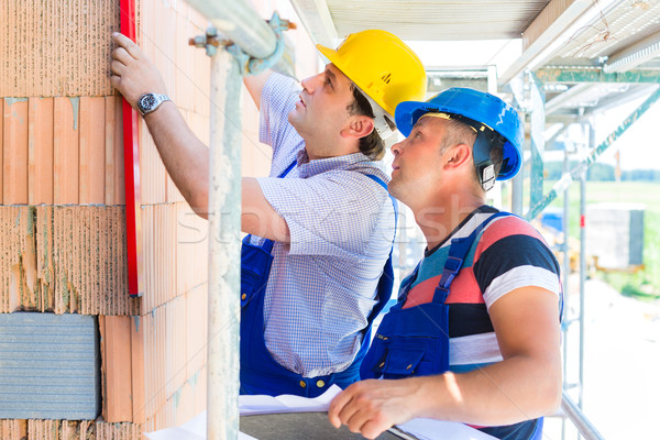 Construction workers on site checking quality Stock photo © Kzenon