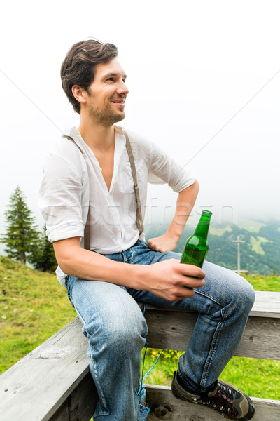 Alps - Man in mountains drinking beer from bottle Stock photo © Kzenon