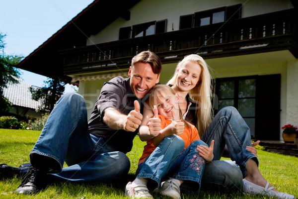 Family sitting in front of their home Stock photo © Kzenon