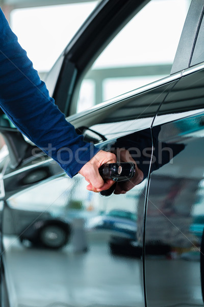 Young man with auto in car dealership Stock photo © Kzenon
