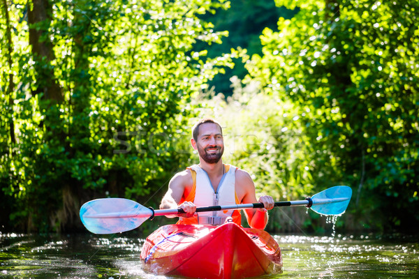 Man paddling with kayak on river for water sport Stock photo © Kzenon