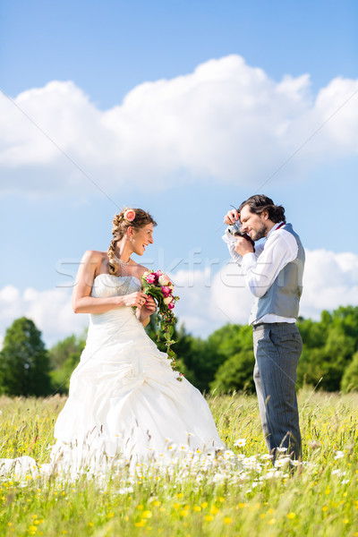 Wedding couple taking pictures on meadow Stock photo © Kzenon