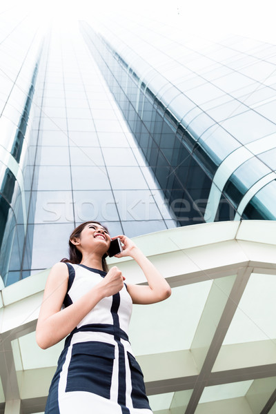 Asian business woman telephoning outside with  phone Stock photo © Kzenon
