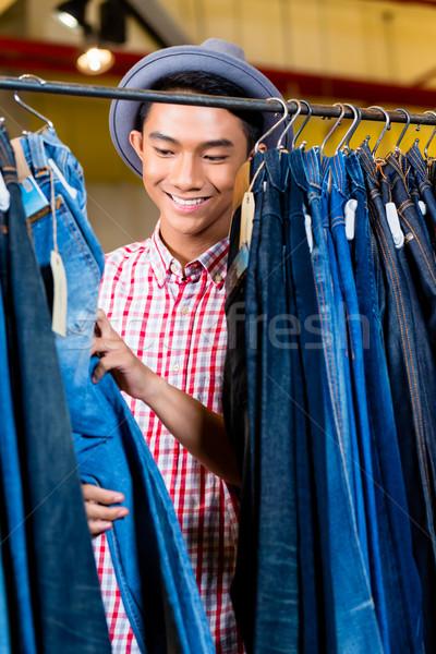Asian man browsing jeans in fashion store Stock photo © Kzenon