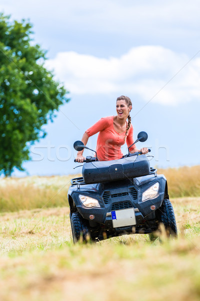 Woman driving off-road with quad bike or ATV Stock photo © Kzenon