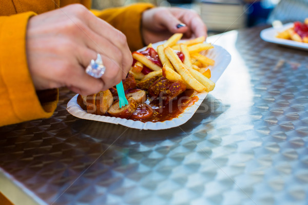 woman eating German Currywurst at stand Stock photo © Kzenon