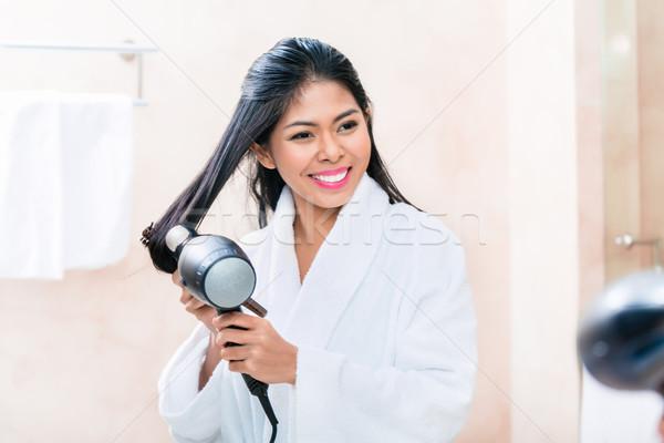 Asian woman in bathroom drying hair Stock photo © Kzenon