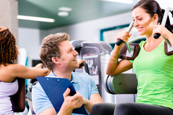 Woman with personal trainer doing sport und fitness Stock photo © Kzenon