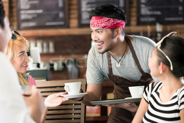 Stock photo: Waiter serving coffee in Asian cafe to women and man